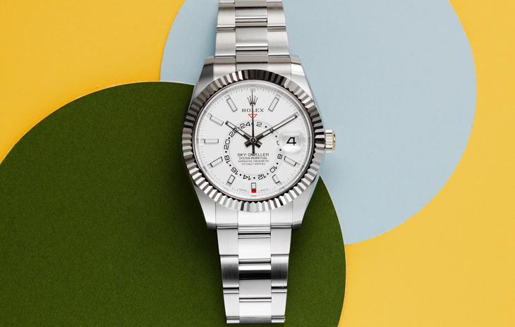 White Rolex Sky Dweller with green, blue, and yellow circles in background