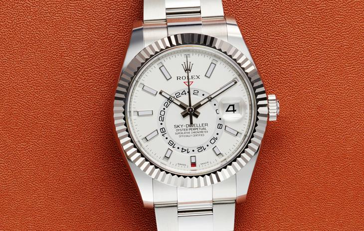 Rolex Sky-Dweller with white dial, fluted bezel, and oyster bracelet on an orange leather background