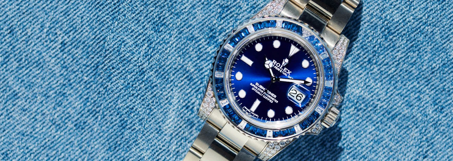 Rolex Submariner with blue dial set with blue gems on the bezel on a denim jacket